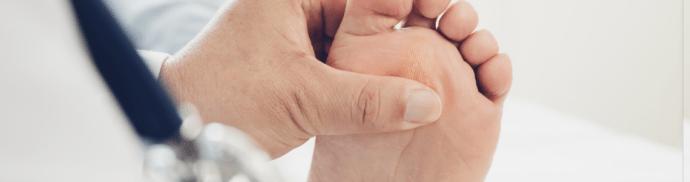 Un médecin examine le pied droit d'un patient